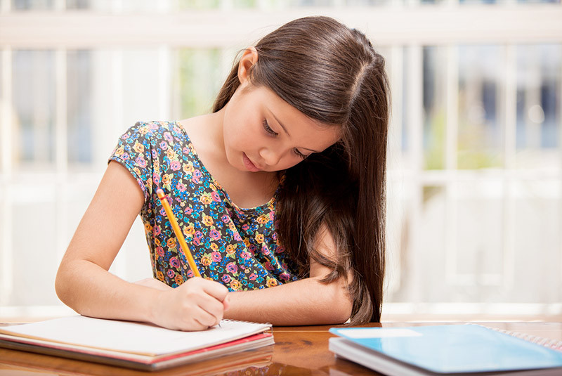 Girl doing homework at dining room table