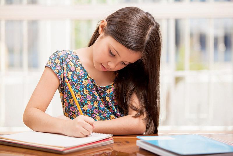 Girl doing homework at dining room table