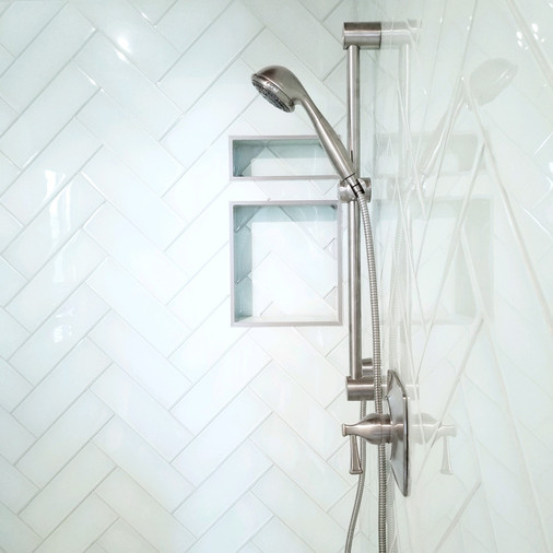 Herringbone glass tile with brushed nickel master bath shower