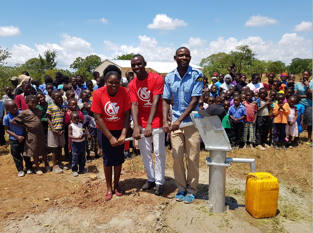 """Pierwsze """"oficjalne"""" krople wodu pompują nauczyciele Lavenda i Righton oraz sołtys wioski Libambami John"""