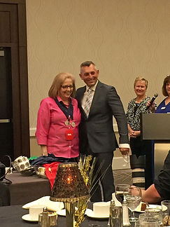 Liliana Shelbrook receives 2 medals from the president of Florida Authors and Publishers Association.
