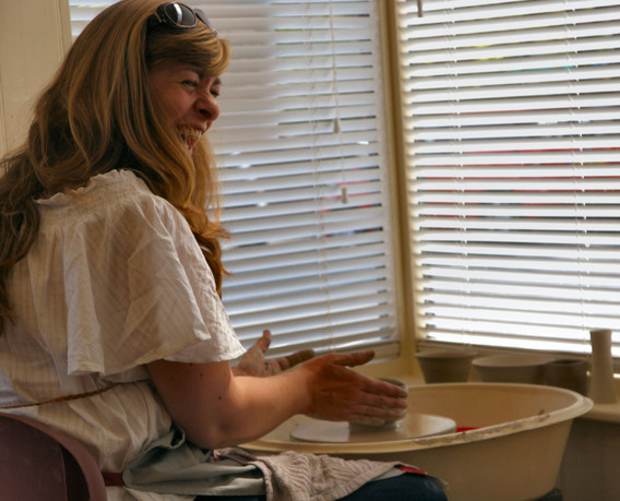 Lady smiling with potter's wheel