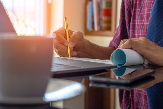 Kvinna skriver med penna vid dator.jpg