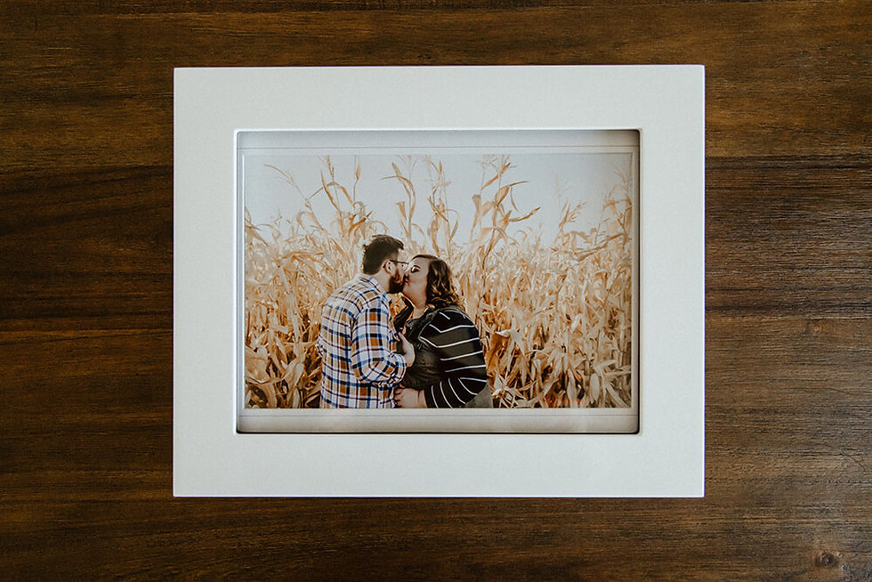 White folio box with matted print of couple in it on a wood table.