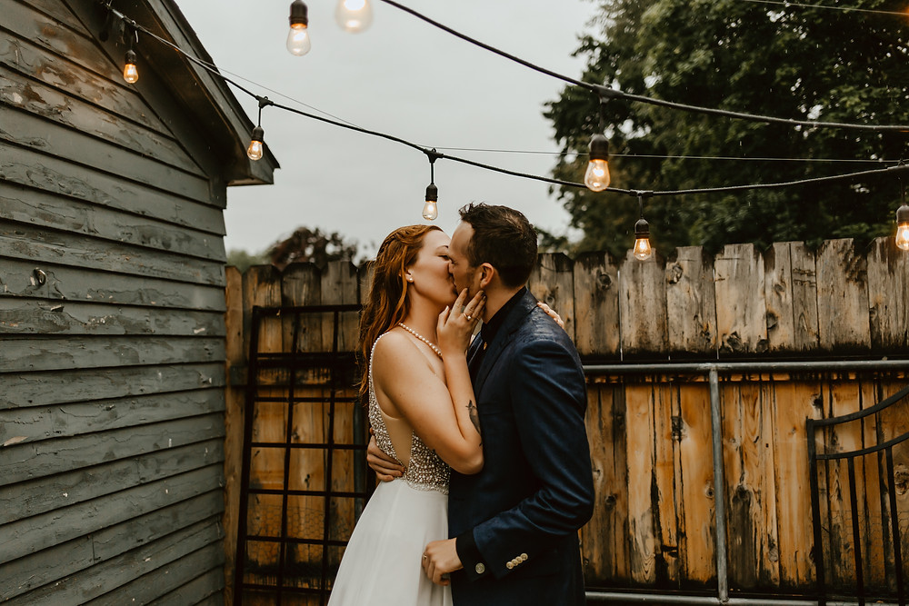 Andy and Nicole kissing under string lights in the rain.
