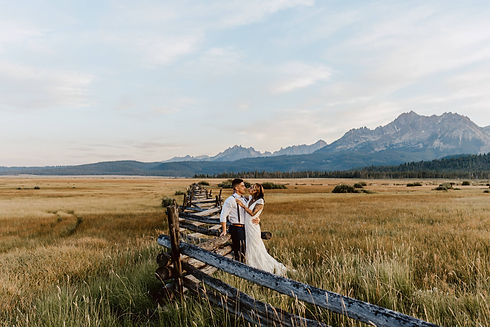 Bride and groom standing near old wooden fence in front of sawtooth mountains in Stanley, Idaho.