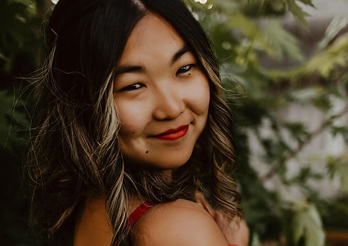Close up of Asian woman with curled black hair and red lipstick.