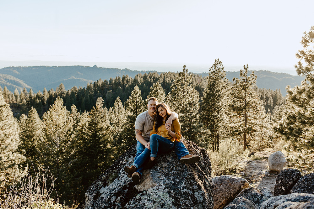 Rylee Driscoll and husband Riley Thomas sit on a rock with trees in the background on Bogus Basin, in Boise, Idaho.