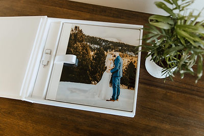 Wedding photo album in white box next to a plant on a wood table.