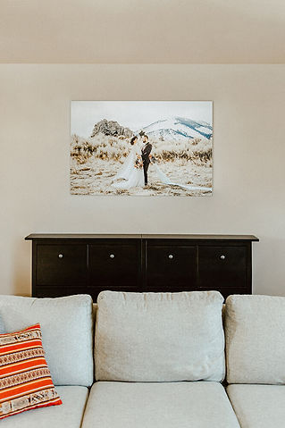 Wedding canvas hanging on a wall behind a couch.
