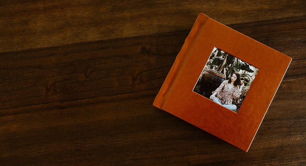 Burnt orange leather album with a square picture of a senior girl in the middle.