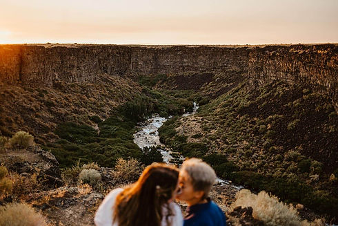 Two women kissing on the edge of a colorful canyon valley.