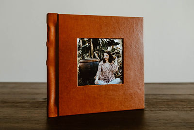 Burnt orange square photo album with a picture cut out of the middle.