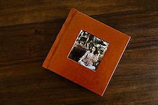 Burnt orange faux leather 8x8 inch album with a senior picture cut out, sitting on a wood table.
