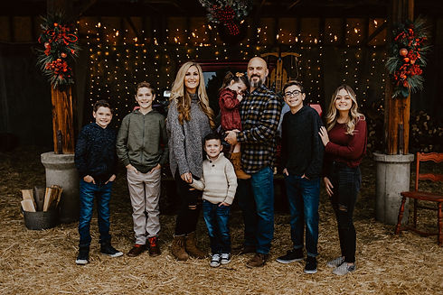 Family of 8 standing together in front of Christmas lights and decorations.