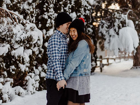 Man and woman hold hands in the snow with matching black beanies.
