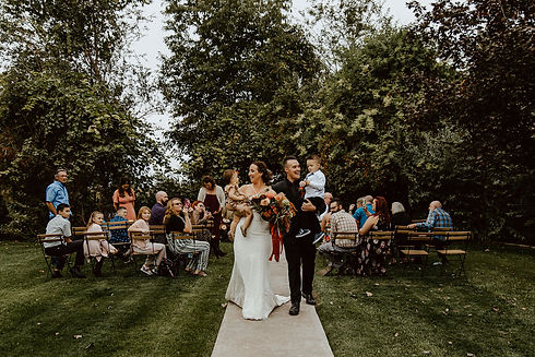 Just married couple walking down aisle while holding their two children.