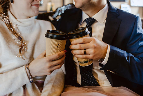 Two hands holding coffee cups cheersing together.