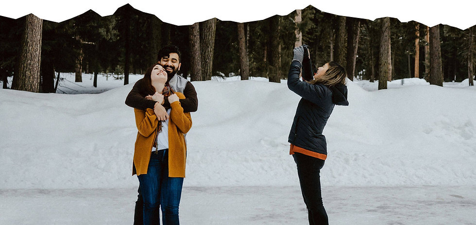 Photographer capturing couple smile and hug each other in the snow.