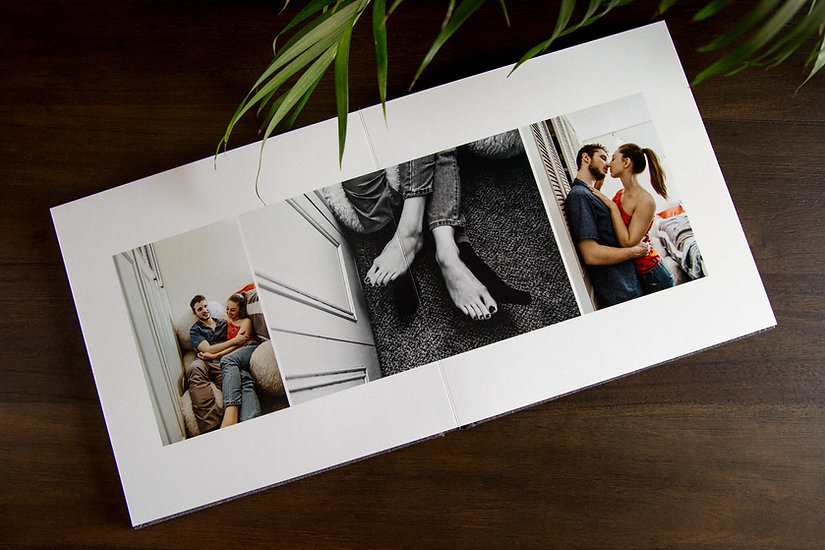 Photography album opened, laying on a wooden table.