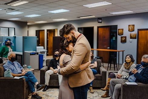 Couple embracing while surrounded by friends and family after saying I do.