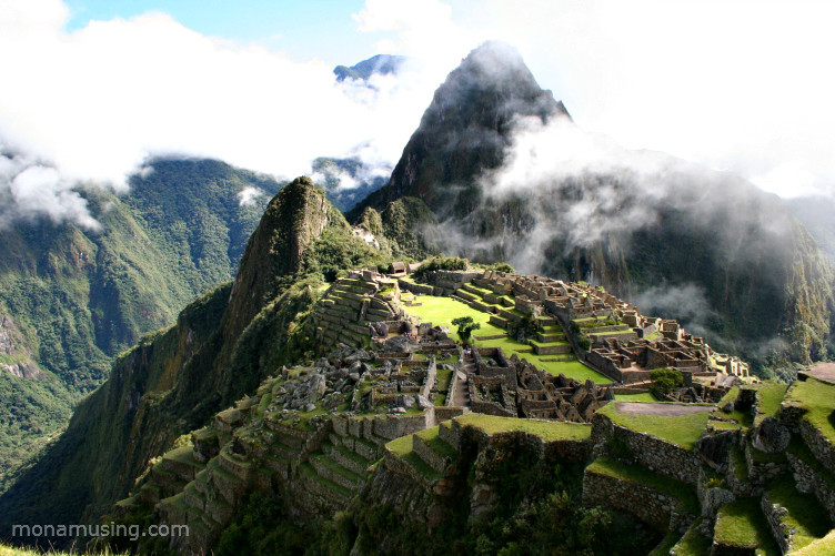 overview of the ruins at Machu Picchu, partially enveloped by clouds