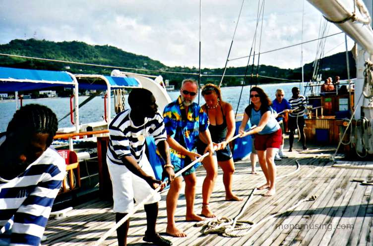 passengers help the crew in raising the sales on a Windjammer barefoot sailing cruise around St. Vincent and the Grenadines