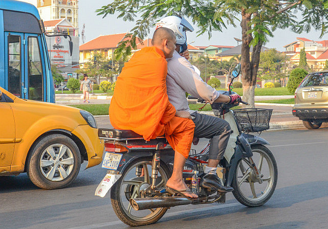 saffron-robed monk riding on the back of a motorcycle in Siem Reap, Cambodia