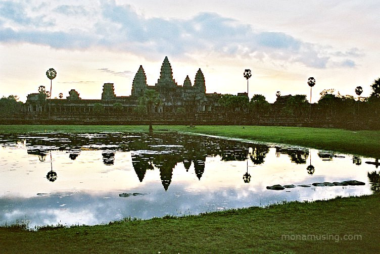 Angkor Wat temple reflected in the water in the early morning light just after sunrise