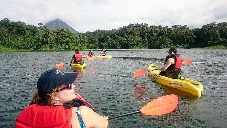 Kayakers on Lake Arenal, with a view of Arenal Volcano in the distance