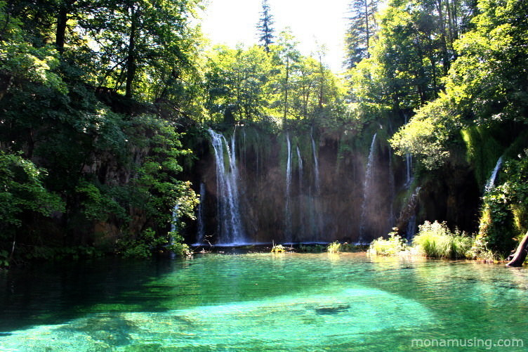 waterfalls and a bright turquoise lake in sunlight at Plitvice National Park, one of the most beautiful sites in Croatia
