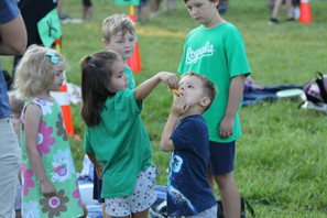 A Brookwood student shares a donut with friends on a laid out blanket at Brookwood's community gathering. Photo by Ben Henschel.