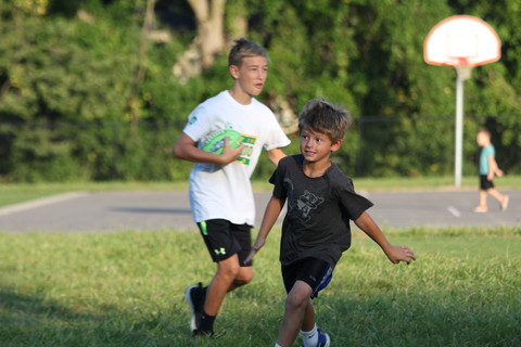 Amid the celebration at the Brookwood community morning, students play football — one taking the carry, and another setting out to block defenders and clear a path with 100-watt eyes. Photo by Ben Henschel.