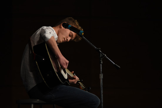 Freshman Fritz Sullivan aligns his hand to strike the right beginning chord for his original song at the 2019 SME Talent Show. Photo by Ben Henschel.