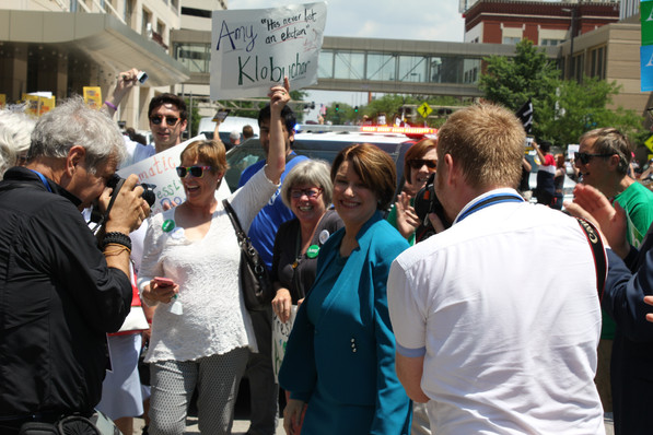 2020 candidate and U.S. Sen. Amy Klobuchar (D-MN) laughs as members of the press capture close-ups and her followers cheer her on with signs and chants. Photo by Ben Henschel.