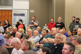 """The crowd of attendees at a gun violence roundtable observe Rep. Sharice Davids — some with high regard, others with """"disappointment,"""" according to an attendee commenting for this story on the condition of anonymity. Photo by Ben Henschel."""