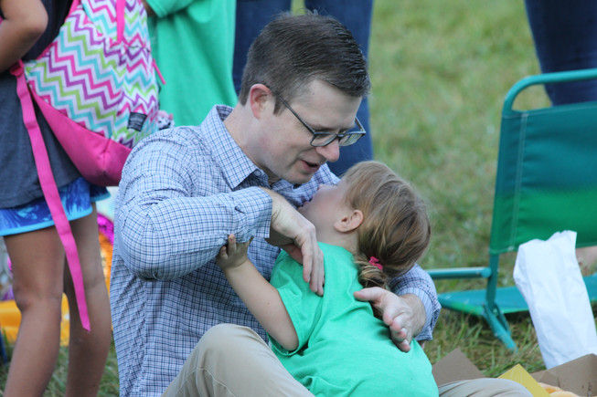 A Brookwood father and his daughter embrace on a blanket toward the far side of the back lawn, across from the playground, paying no mind to the Westboro Baptist Church's protests at the front of the school. Photo by Ben Henschel.