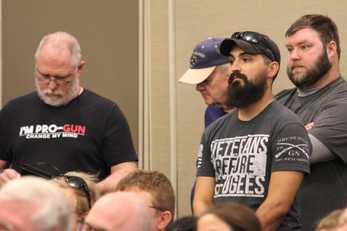 """Outspoken critics of the panel's remarks take notes at a gun violence roundtable, emote their contempt and look on with """"a lot of confusion, because what they were contradicting themselves,"""" one attendee of the gun violence roundtable said. Photo by Ben Henschel."""