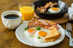 American breakfast with sunny side up eggs, bacon, toast, pancakes, coffee and juice, wood