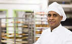 Positive man baker carrying tray with fresh baked bread at bakery kitchen