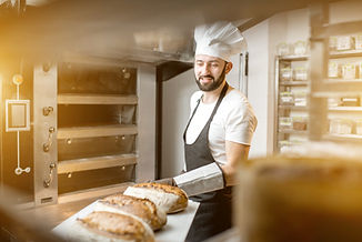 Baker carrying shovel with fresh baked breads standing near the professional oven in the b