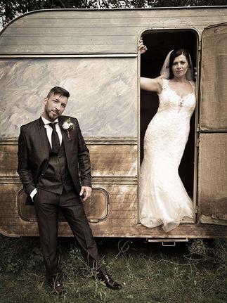 Photo de mariage, couple près d'une caravane.
