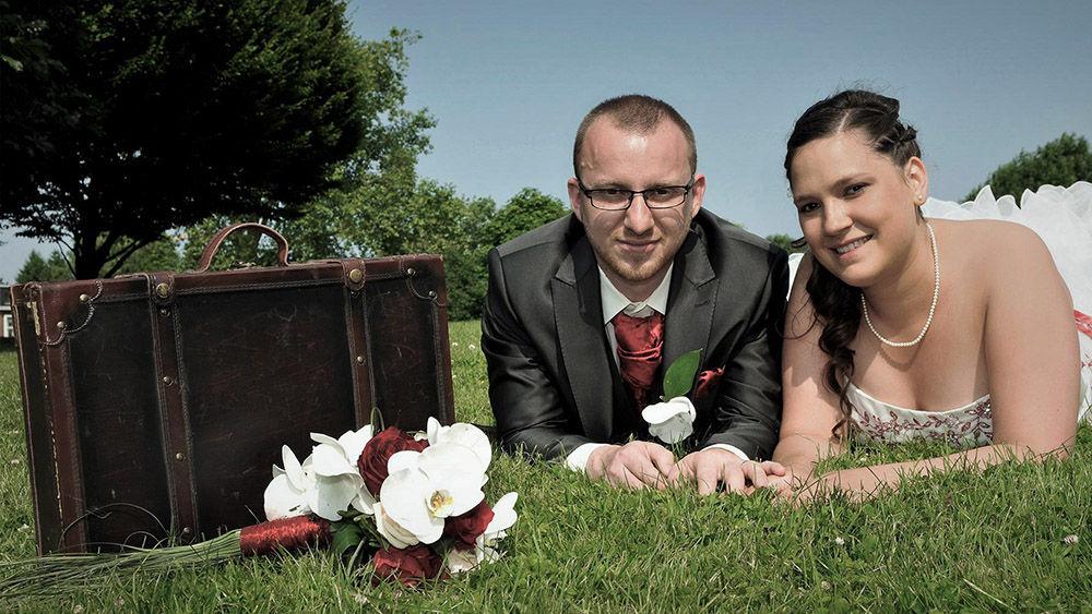 Mariés sur l'herbe avec une valise