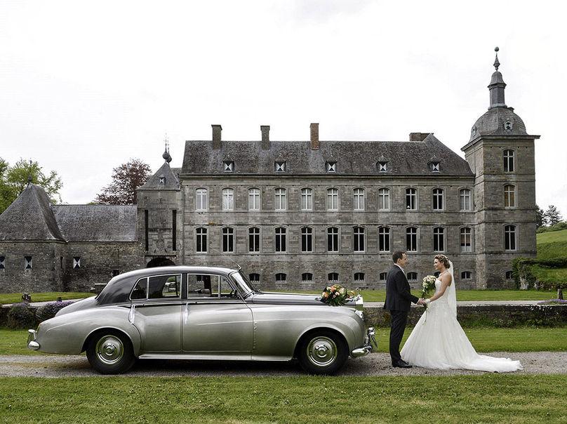 Photo de mariage avec voiture de luxe et château en arrière-plan