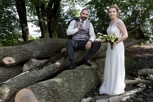 Photographe mariage, couple avec troncs d'arbres.