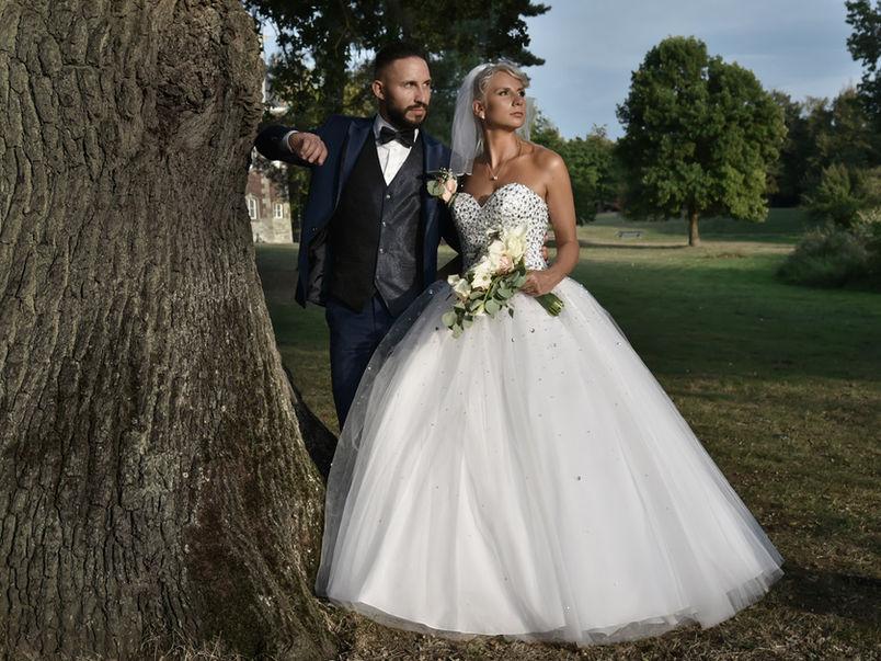 Couple de mariés près d'un arbre