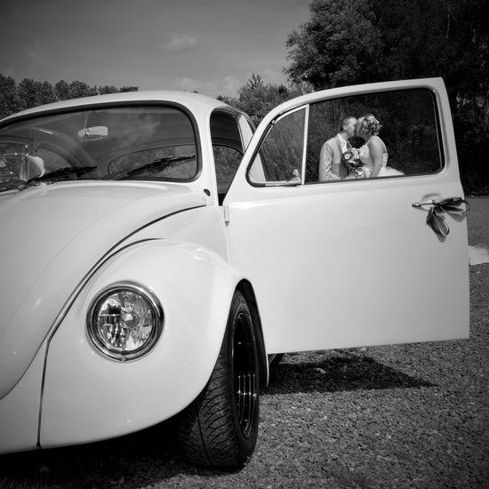 Mariés photographiés avec voiture coccinelle