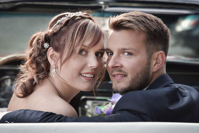 Portrait d'un couple de mariés dans une voiture