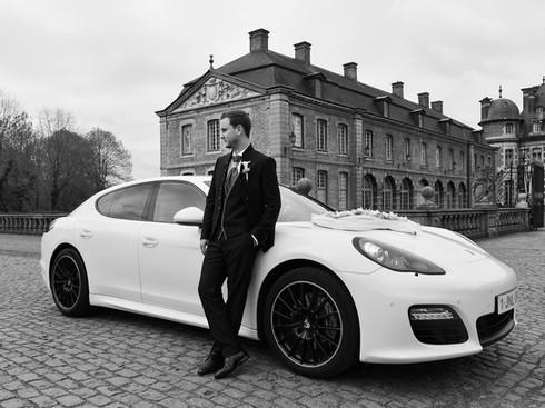 Photo de mariage, pose du marié près de sa voiture.