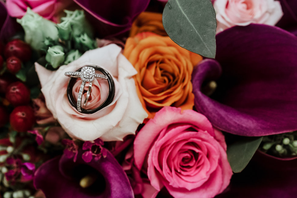 Wedding ring trio sitting on a pink rose in a colorful bouquet.